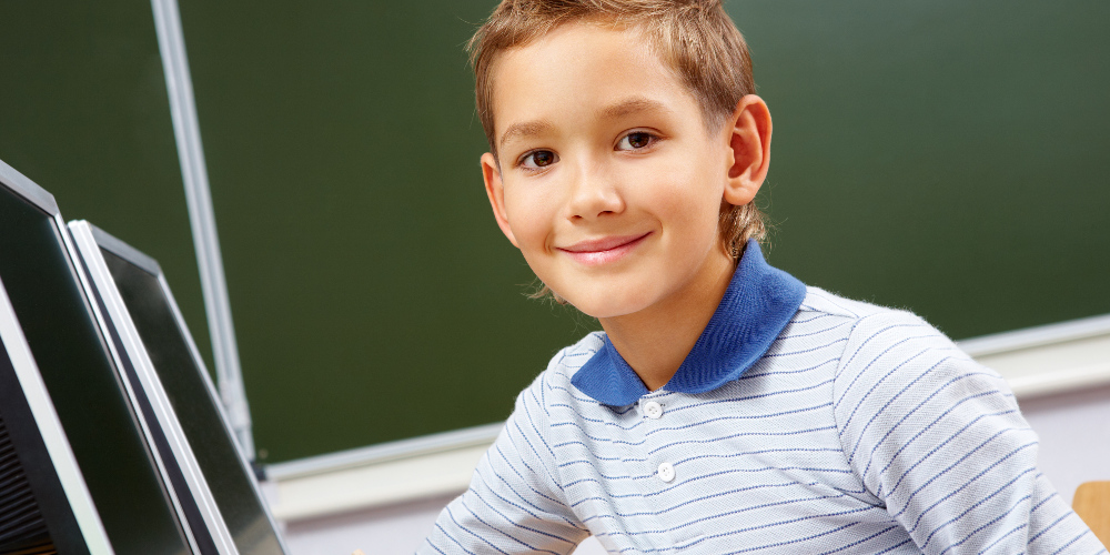 Lächelnder Junge vor einem Laptop