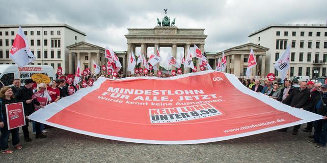 Demonstranten mit Mindestlohn-Transparent vor Brandenburger Tor Berlin