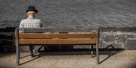 alter Mann sitzt allein auf einer Holzbank