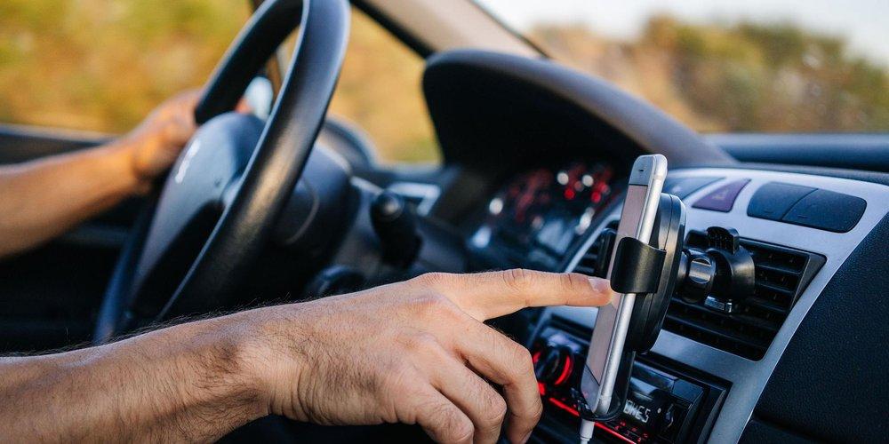 Cockpit eines Autos, Fahrer hat eine Hand am lenkrad, mit der anderen bedient er ein Smartphone