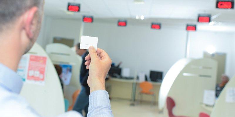 Mann hält in Warteraum eines Amtes / Bürgeramtes Wartenummern-Zettel hoch