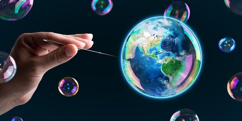 Nadel bringt eine Seifenblase mit Weltkugel darin (fast) zum Platzen