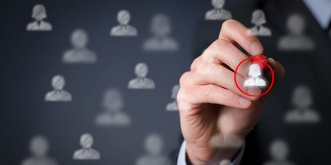 Hand kreist mit rotem Stift eines von vielen Personensymbolen ein