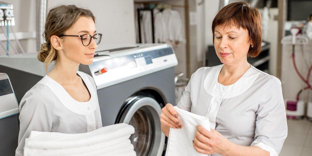 zwei Frauen vor einer Indsutriewaschamschine falten saubere Wäschestücke zusammen