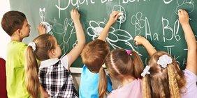 Kinder schreiben an Schultafel
