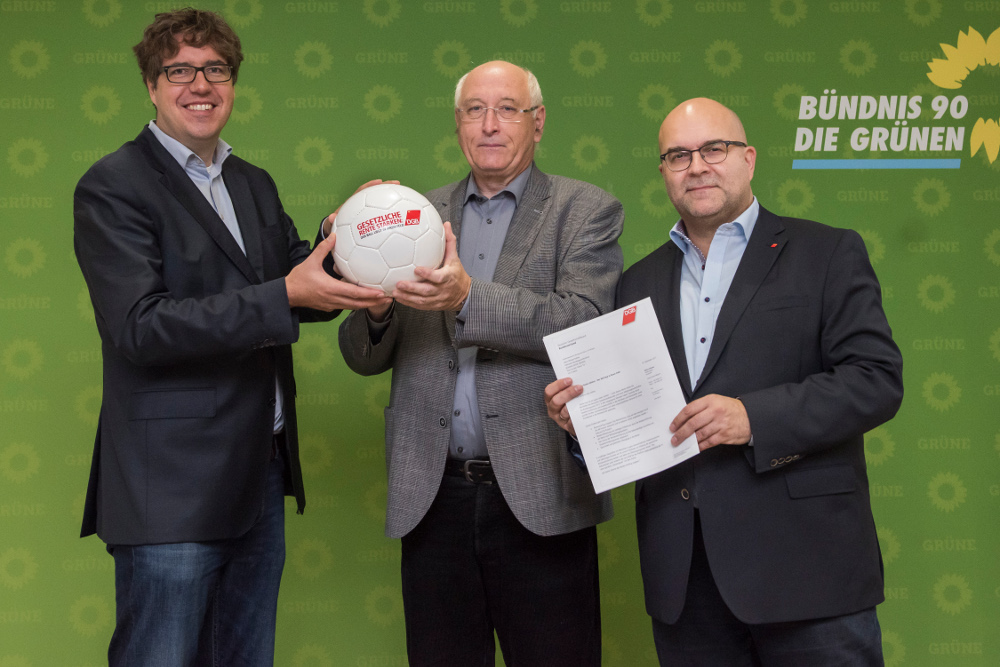 Drei Männer halten gemeinsam einen Fußball vor einer Rückwand der Partei Bündnis 90/Die Grünen