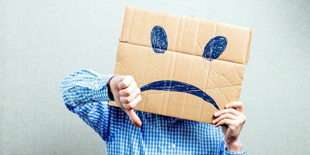 Mann mit Pappmaske vor Gesicht (traurig)