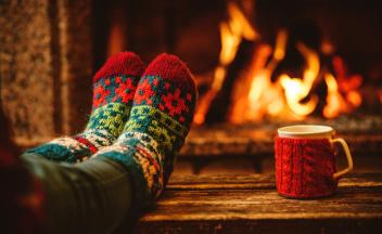 Füße in Wollsocken mit dampfender Tasse vor Kaminfeuer