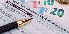 Nahaufnahme/Ausschnitt eines Behördenformulars (mit einem Abschnitt zur Riester-Rente); darauf ein Kugelschreiber, Euro-Scheine und Euro-Münzen