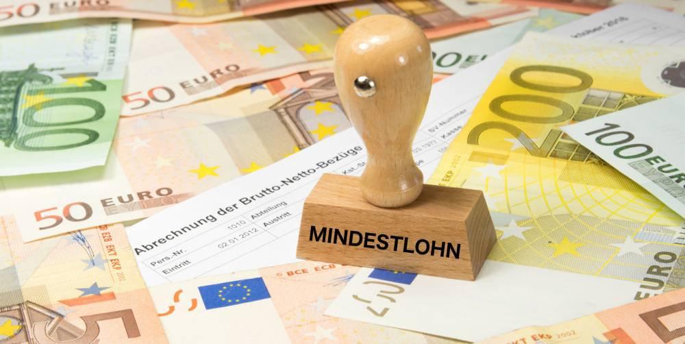 """Stempel mit der Aufschrift """"Mindestlohn"""" und mehrere Euro-Banknoten"""