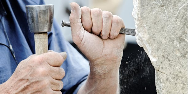 Arbeiten mit Hammer und Meißel an Stein