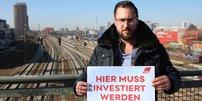 Crispin Kallinger (EVG) mit Schild: Hier muss investiert werden, auf Brücke in Berlin vor Fernsehturm