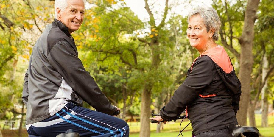 Ein älteres Paar mit Fahrrädern im Park