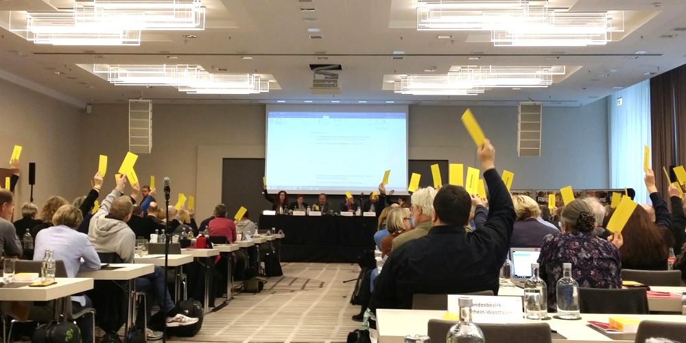 Saal mit Delegierten, die gelbe Stimmkarten heben