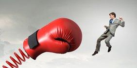 Übergroßer Boxhandschuh und ein wegfliegender Mann im Anzug