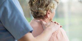 Pfleger legt Seniorin Hand auf die Schulter