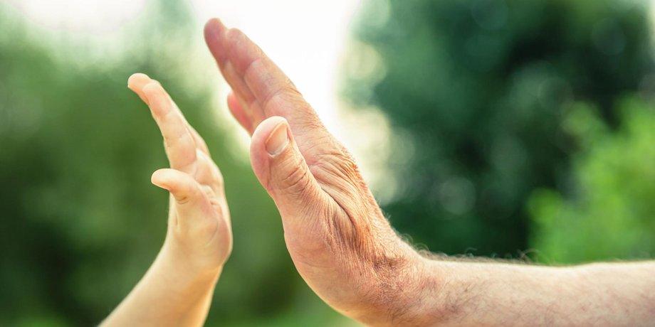 Hand eines Kindes und Hand eines älteren Mannes