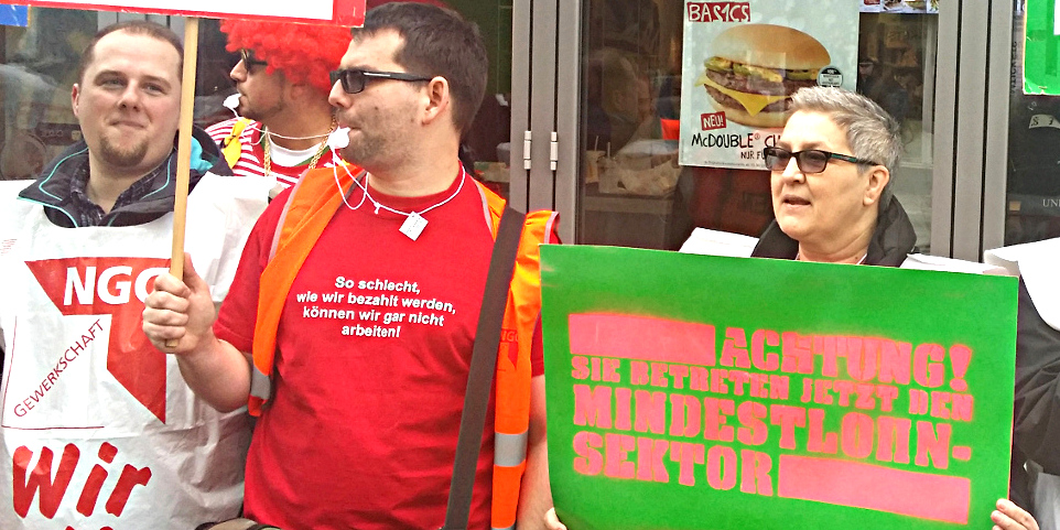 Drei Demonstranten vor einer McDonalds-Filiale