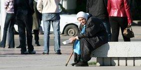 ältere Frau sitzt bettelnd auf einer Steinkante
