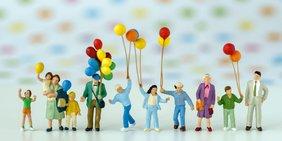 Mehrere Miniatur-Figuren mit Luftballons
