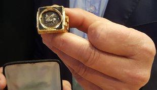 Nahaufnahme eines goldenen Rings, gehalten von Daumen und Mittelfinger einer Hand