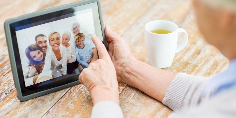 Nahaufnahme Hände eines älteren Menschen halten Tablet, das eine Familie zeigt