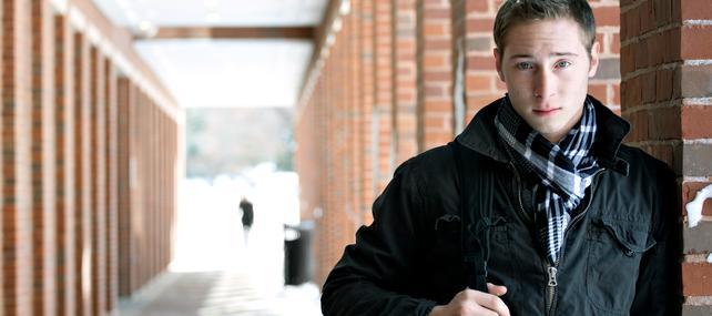 Junger Mann mit Rucksack an Ziegelsteinsäule