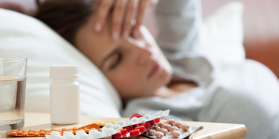 Kranke Frau im Bett mit Medikamenten
