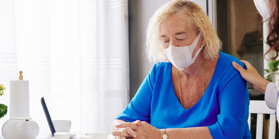 ältere Frau sitzt alleine am Tisch mit Nasen- und Mundschutz