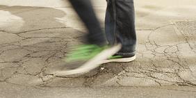 Schnell laufender Fußgänger auf Straße mit vielen Schlaglöchern