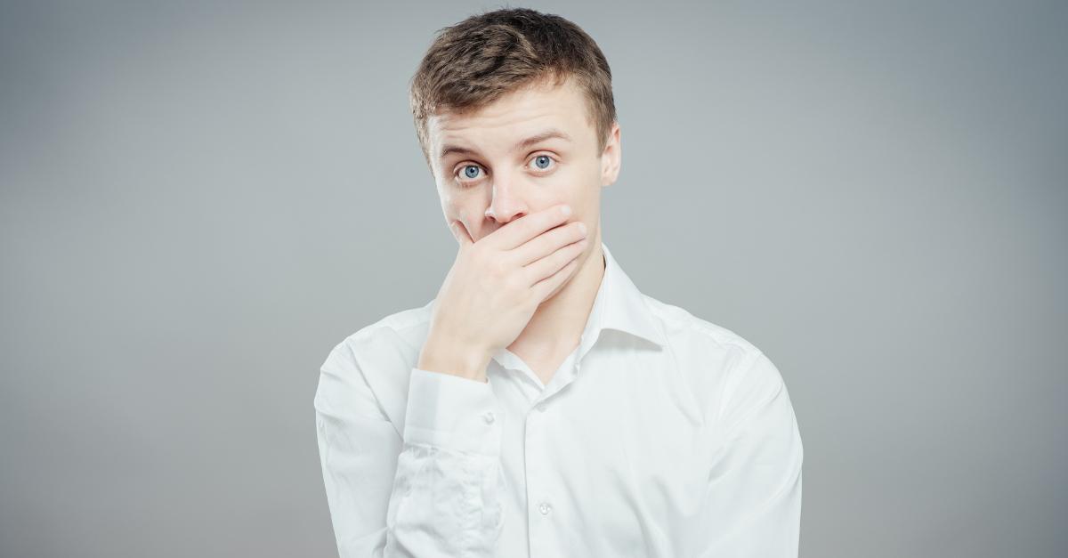 Junger Mann im weißen Oberhemd hält nachdenklich Hand vor den Mund, grauer Hintergrund