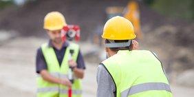 Zwei Männer in Arbeitskleidung vermessen eine Baustelle