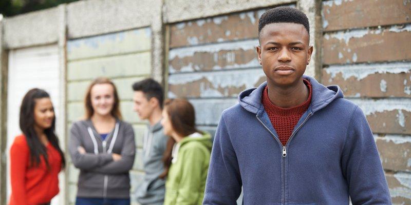 Gruppe Jugendlicher unterhält sich im HIntergrund; im Vordergrund ein einzelner Jugendlicher (Person of Color)