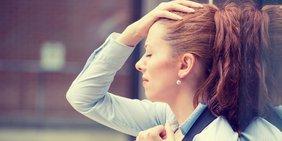Frau fasst sich erschöpft an die Stirn