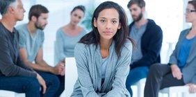 Junge Frau vor einer Diskussionsrunde