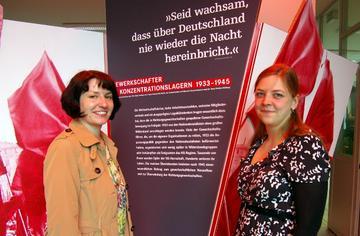 Alexandre Kruse und Juliane Jurewizc vor der Eröffnungstafel der Ausstellung