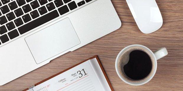 Laptop, Kaffeetasse und Kalender auf einem Holztisch