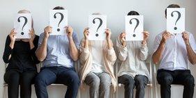 Fünf Menschen sitzen auf Stühlen und halten sich Schilder mit Fragezeichen vor das Gesicht