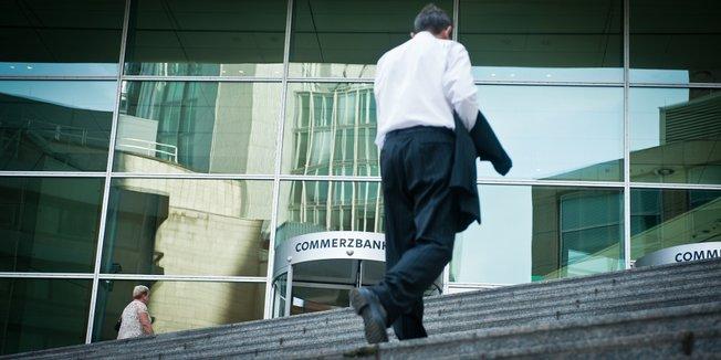 Mann im Anzug mit Jacket über dem Arm geht Treppe zu einem Gebäude mit Glasfassade der Commerzbank hoch