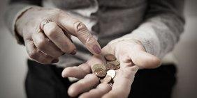 Hand von älterer Dame hält mehrere Münzen