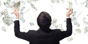 Mann im Anzug wirft Geldscheine in die Luft