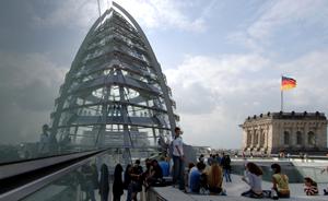 Personengruppe neben der Glaskuppel auf der Dachterasse des Bundestages, Berlin. Im Hinergrund weht eine Deutschland-Fahne.