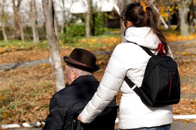 Frau schiebt Mann in Rohlstuhl