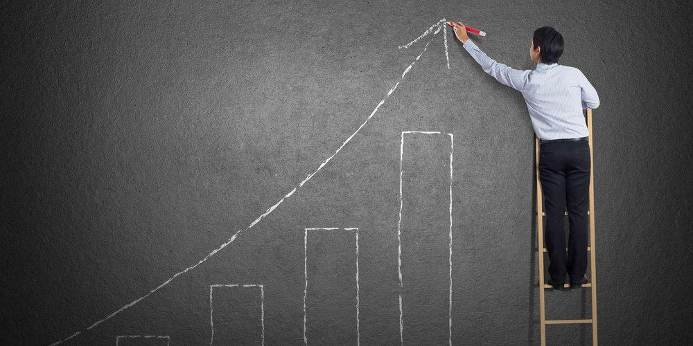 Geschäftsmann steht auf einer Leiter und zeichnet Wachstumskurve