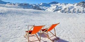 Zwei Liegstühle im Schnee auf einem Bergplateau
