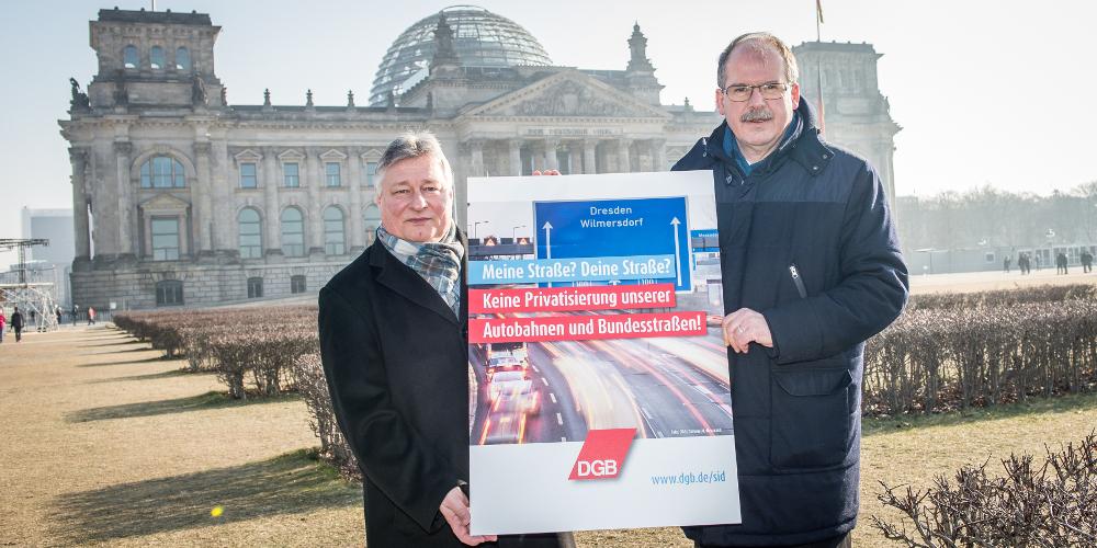Zwei Personen halten vor dem Reichstag in Berlin ein Protest-Plakat gegen Autobahn-Privatisierungen hoch