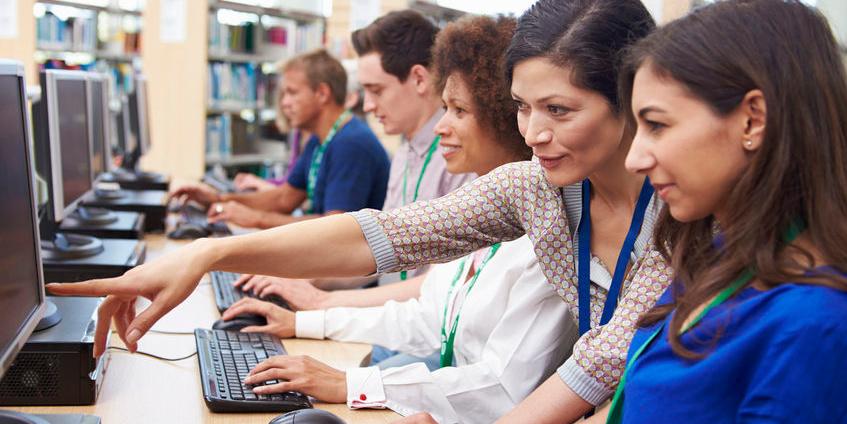 Mehrere Menschen vor Computern bei einer Weiterbildung
