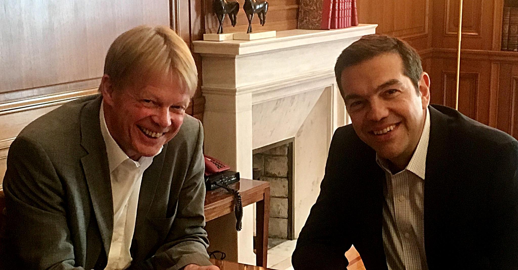 Der DGB-Vorsitzende Reiner Hoffmann und der griechische Ministerpräsident Alexis Tsipras; nebeneinander an Tisch sitzend; lächelnd in Kamera schauend