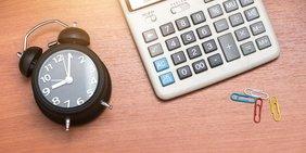 Wecker und Taschenrechner auf Schreibtisch