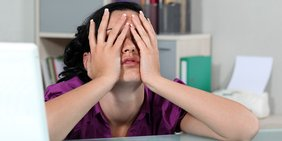 Frau sitzt am Schreibtisch mit Händen im Gesicht